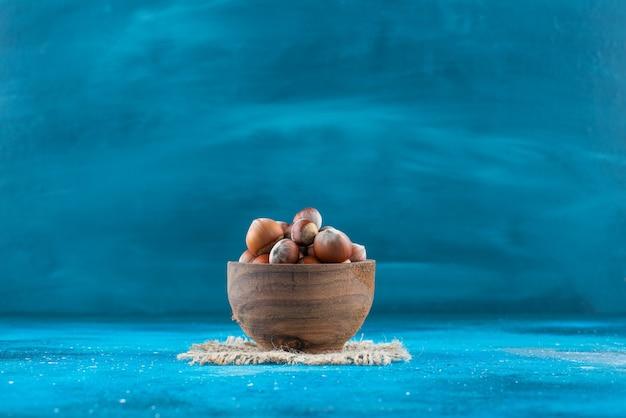 Orzechy laskowe w misce na fakturze na niebieskiej powierzchni