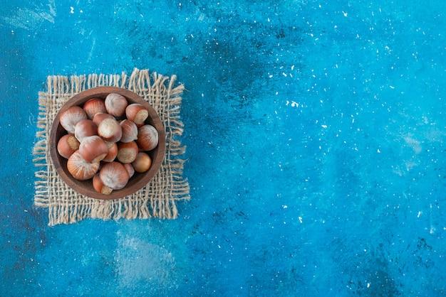 Orzechy laskowe w misce na teksturze, na niebieskim stole.