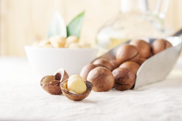 Orzechy Makadamia Rano Rozrzucone Na Lekkim Stole. Premium Zdjęcia