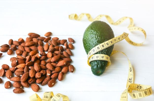 Orzechy migdałowe i awokado z centymetrem. dieta odchudzająca. zdrowy tryb życia. koncepcja wegańska. odpowiednie odżywianie. jedzenie sportowe.