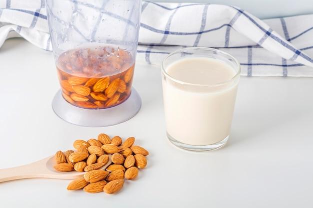 Orzechy mleko i migdały w szklankach i drewniana łyżka z ściereczką kuchenną na białym stole