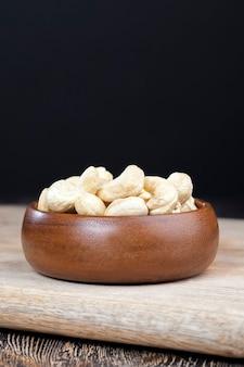 Orzechy nerkowca na starym drewnianym stole i w drewnianej misce, zbliżenie dużej liczby orzechów nerkowca na stole i na drewnianej powierzchni w drewnianym talerzu