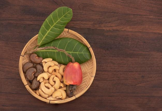 Orzechy nerkowca, owoce, nasiona i zielone liście na starym drewnianym stole.