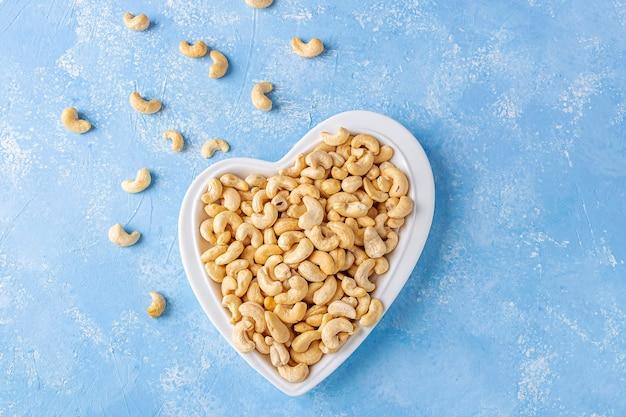 Orzechy nerkowca w talerzu w kształcie serca. zdrowe wegetariańskie przekąski.