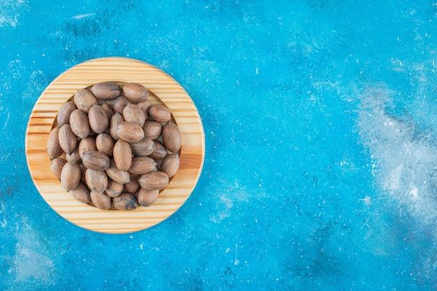 Orzechy pekan na drewnianym talerzu na niebieskiej powierzchni