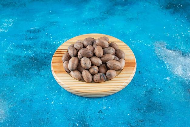 Orzechy pekan na drewnianym talerzu, na niebieskim stole.