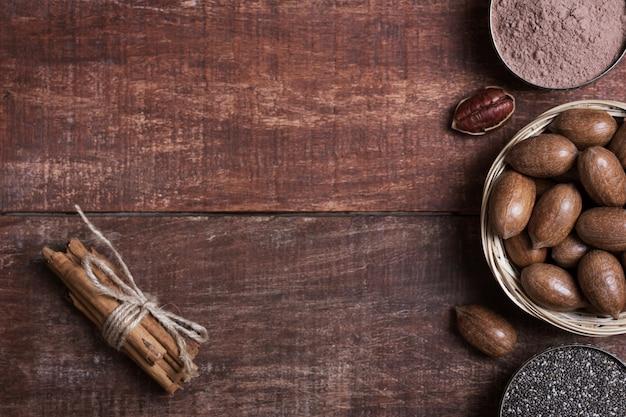 Orzechy pekan, nasiona chia i kakao w miskach na drewnianym stole