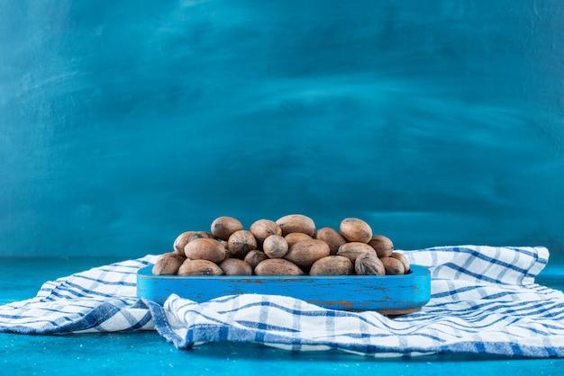Orzechy pekan w drewnianym talerzu na ściereczce, na niebieskim stole.