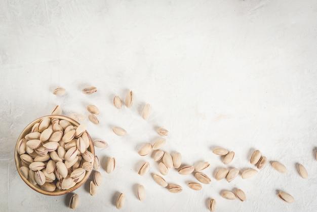 Orzechy pistacjowe na białym kamiennym stole, w misce i rozrzucone. skopiuj widok z góry