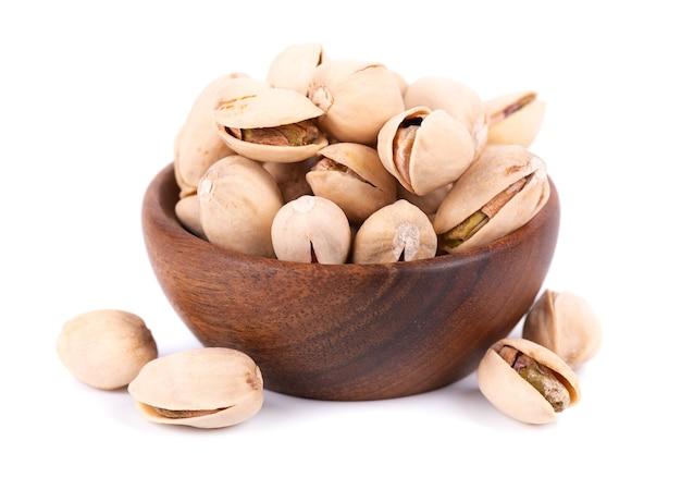 Orzechy pistacjowe, na białym tle w drewnianej misce, na białym tle. solone prażone pistacje.
