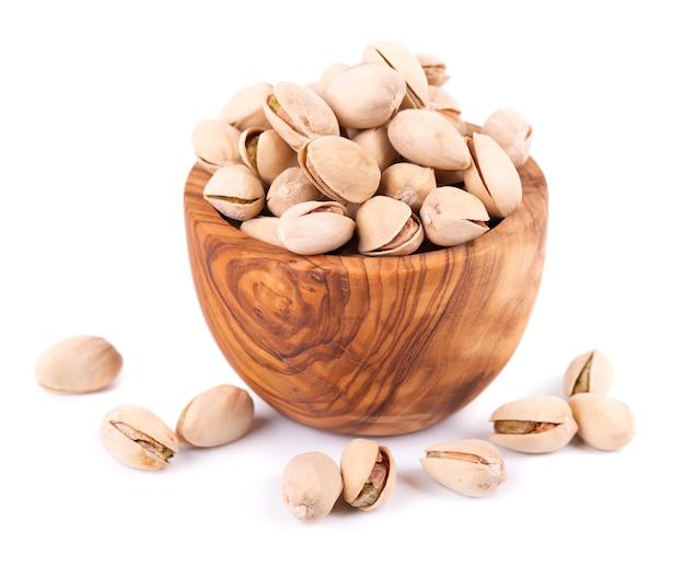 Orzechy pistacjowe, na białym tle w misce oliwek, na białym tle. solone prażone pistacje.
