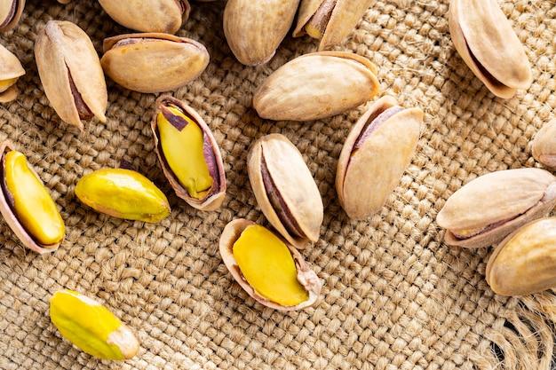 Orzechy pistacjowe na płótnie. solone, prażone zielone pistacje na tle worze. zdrowa przekąska. widok z góry