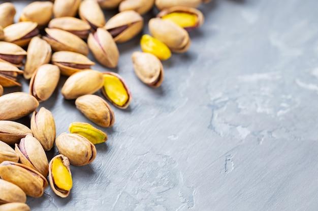 Orzechy pistacjowe na szarym tle. pieczone solone pistacje w łupinach. pojęcie zdrowego odżywiania wegańskie jedzenie. skopiuj miejsce. płaskie ułożenie