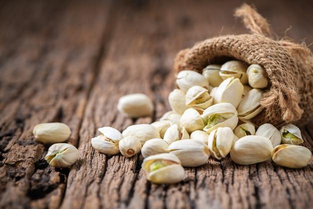 Orzechy pistacjowe na tle starego drewna. przekąski i koncepcja zdrowych orzechów