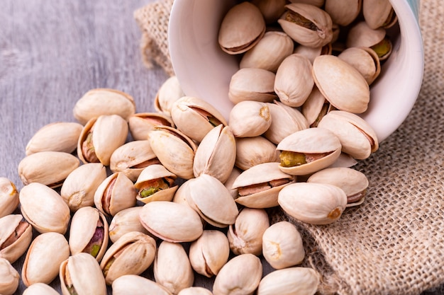 Orzechy pistacjowe w białej ceramicznej misce na drewnianym stole.