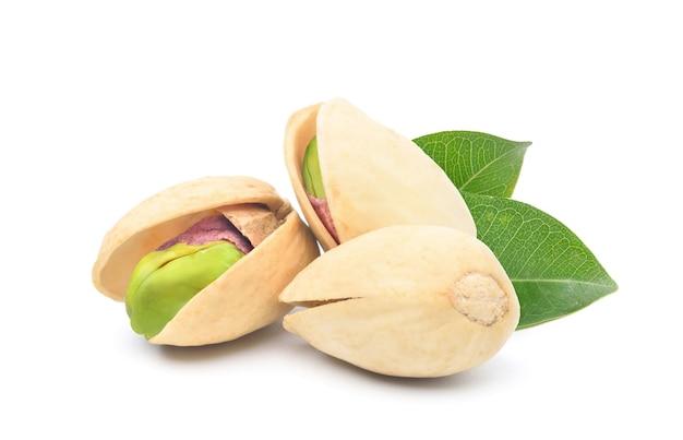 Orzechy pistacjowe z zielonymi liśćmi na białym tle.
