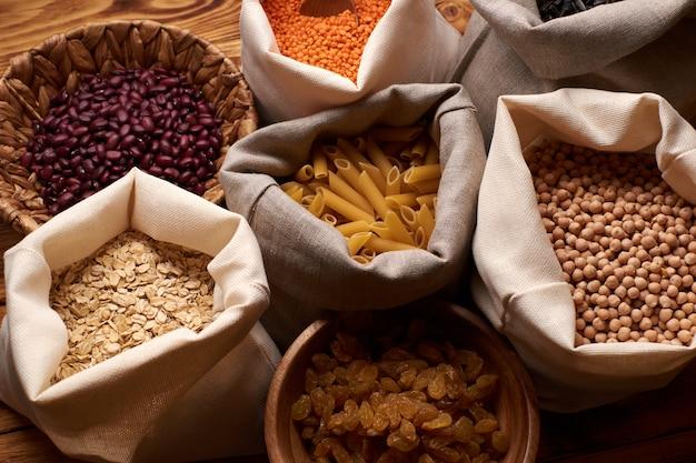 Orzechy, suszone owoce i warzywa w eko-bawełnianych woreczkach na drewnianym stole