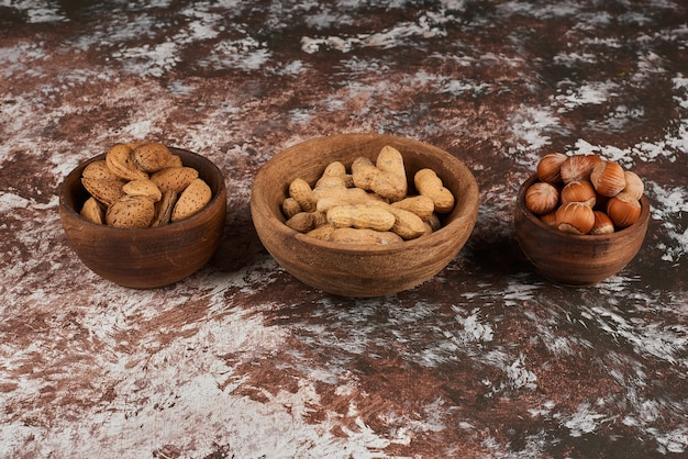Orzechy w drewnianych kubkach na marmurze.