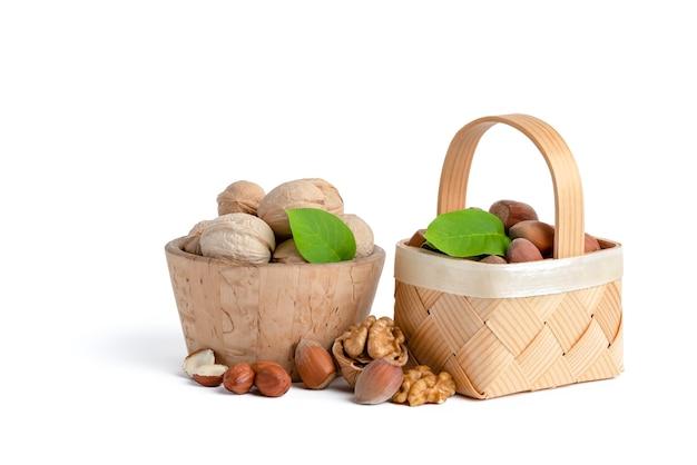 Orzechy włoskie i laskowe różnych odmian leżą w drewnianych spodkach i koszach na białym tle. w pobliżu zielone liście, orzechy włoskie i łuskane orzechy laskowe.