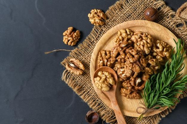 Orzechy włoskie i liść rozmarynu w płycie z drewna na tle czarnym stole.