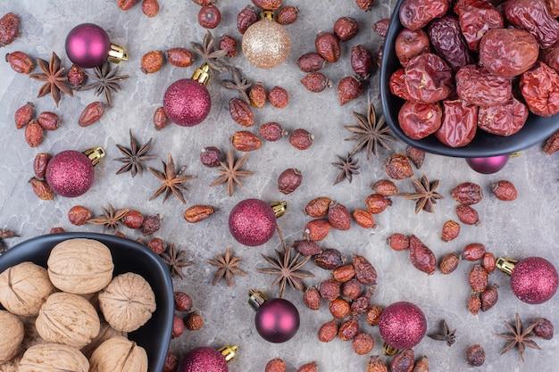 Orzechy włoskie i owoce dzikiej róży w miseczkach z bombkami.