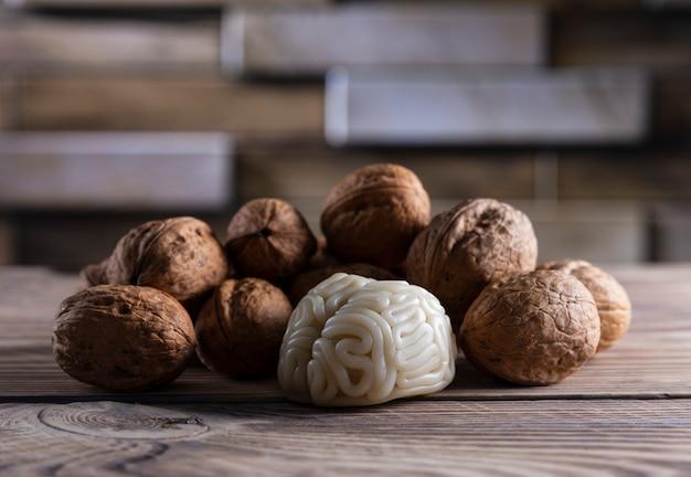 Orzechy włoskie lubią zdrową żywność dla mózgu. kształt ludzkiego mózgu otoczony jest jądrami orzecha włoskiego. symbolizuje podobieństwo mózgu do orzechów włoskich i udowodnioną skuteczność jako zdrowej żywności dla mózgu.