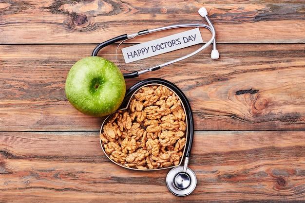 Orzechy włoskie, pudełko, stetoskop i jabłko. przyjazne gratulacje dla lekarza.