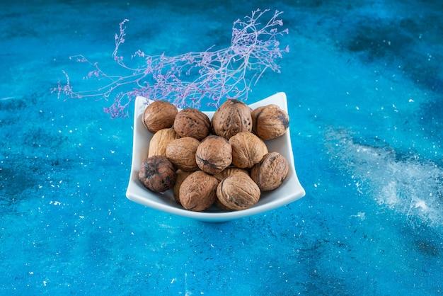 Orzechy włoskie w łupinach w misce, na niebieskim stole.