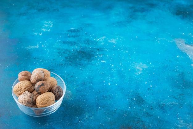Orzechy włoskie w łupinach w szklanej misce, na niebieskim stole.