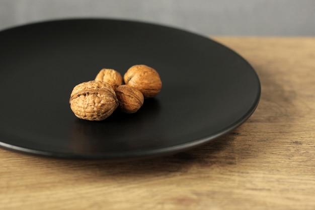 Orzechy włoskie w skorupce na czarnym talerzu
