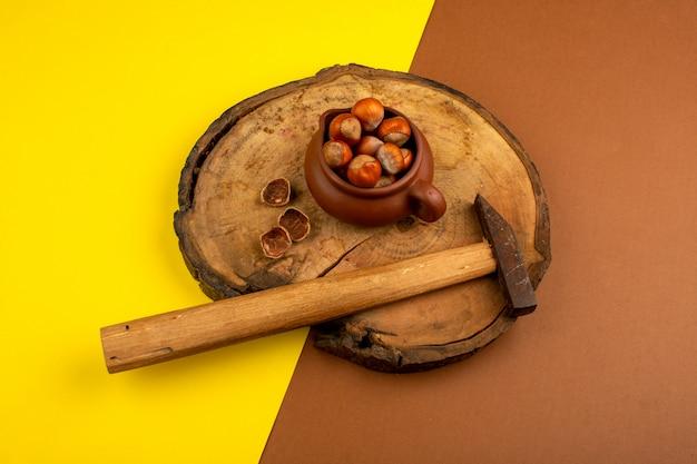 Orzechy wraz z młotem na drewnianym biurku i żółto-brązowy