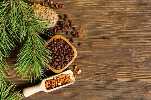 Orzeszki piniowe w misce i szyszka na drewnianym stole, miejsce na tekst