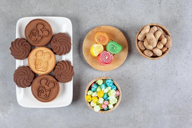 Orzeszki ziemne, cukierki popcorn, marmolady i ciasteczka na marmurowym tle. wysokiej jakości zdjęcie