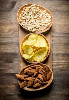 Orzeszki ziemne, frytki i okruchy w miseczkach. na drewnianym tle