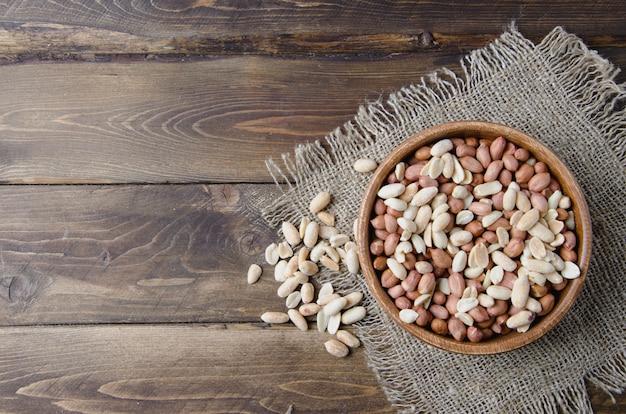 Orzeszki ziemne i migdały na drewnianej misce i konopie