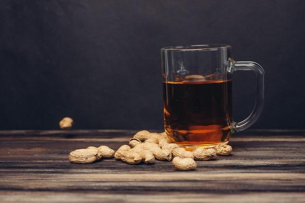 Orzeszki ziemne kufel piwa w muszlach na drewnianym tle snack bar