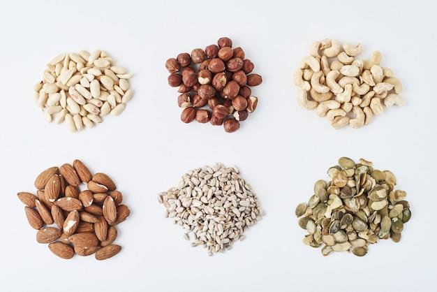 Orzeszki ziemne, orzechy nerkowca, orzechy laskowe, migdały, nasiona dyni i nasiona słonecznika na białym tle odizolowane