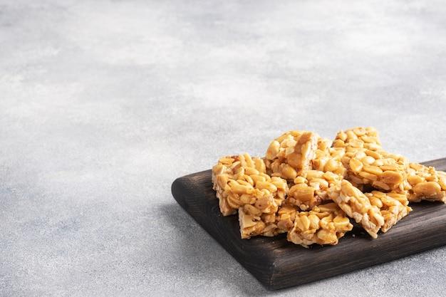 Orzeszki ziemne w glazurze cukrowej, orientalna słodycz krucha. kozinaki są rozbijane na kawałki na drewnianej desce, kopia przestrzeń.