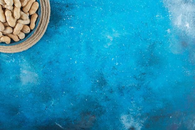 Orzeszki ziemne w łupinach w drewnianej tablicy na trójnogu na niebieskiej powierzchni