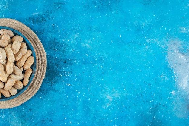 Orzeszki ziemne w łupinach w drewnianym talerzu na trivet, na niebieskim stole.