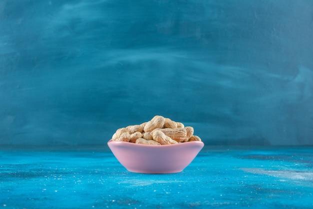 Orzeszki ziemne w łupinach w talerzu, na niebieskim stole.