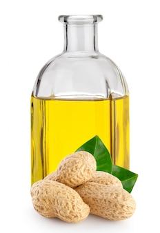 Orzeszki ziemne z liśćmi i olejem orzechowym w butelce