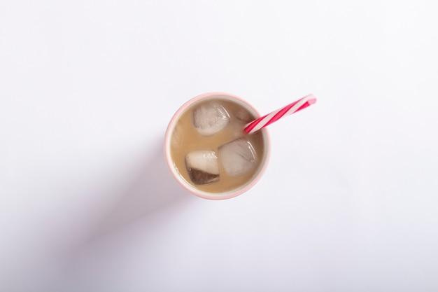 Orzeźwiająca i orzeźwiająca kawa z lodem w szklance na jasnej białej powierzchni. koncepcja kawiarnia, gasi pragnienie, lato. leżał płasko, widok z góry