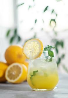 Orzeźwiająca lemoniada mrożona w szklance z plasterkiem cytryny i listkami mięty z owocami cytryny
