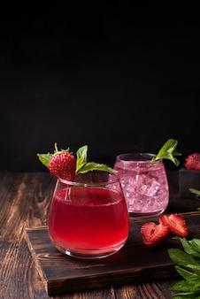 Orzeźwiająca lemoniada truskawkowa z liśćmi mięty, woda owocowa na ciemnym tle drewnianych, koncepcja letnich napojów, z bliska.