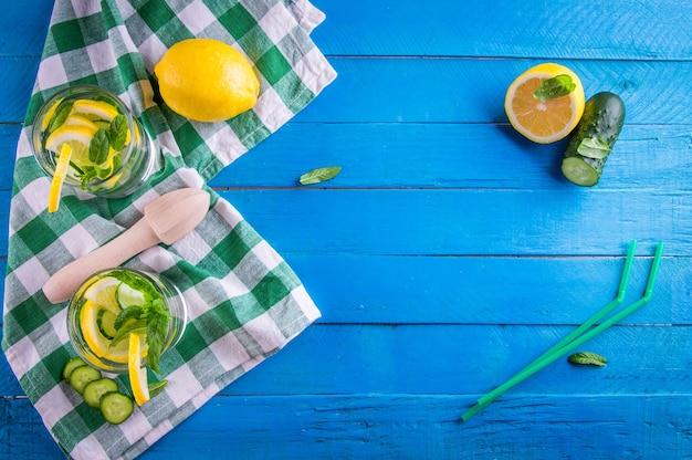 Orzeźwiająca lemoniada z cytryny, ogórka, limonki i mięty na niebieskim tle. letni napój. zdrowe napoje organiczne