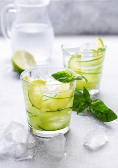 Orzeźwiająca letnia domowa lemoniada z limonki, cytryny, ogórka i bazylii z lodem w szkle na starym betonowym tle. selektywne skupienie.