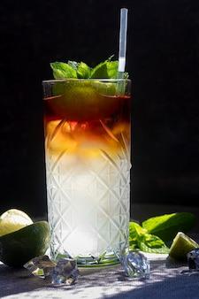 Orzeźwiające letnie koktajle z plasterkiem limonki. napój alkoholowy. przyozdobiony gałązką mięty, cytrusów i kostek lodu. w barze.