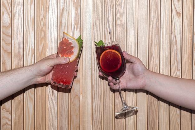 Orzeźwiające letnie koktajle z plasterkiem pomarańczy i grejpfruta. napój alkoholowy. przyozdobiony gałązką mięty i kostkami lodu. w barze.