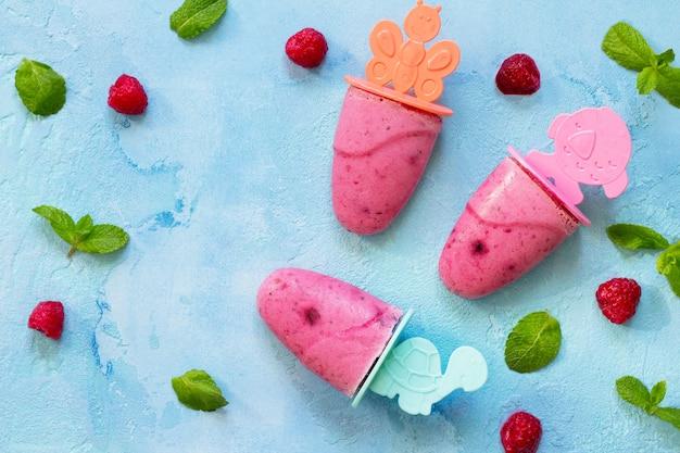 Orzeźwiające lody dla dzieci popsicles sorbet malinowy na niebieskim betonowym tle c